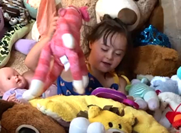 Image Description: A young girl is surrounded by stuffed toys and dolls.