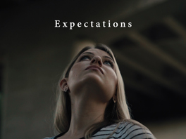 """Image Description: A young woman looks out into the distance. The photo is taken from the ground. The title """"Expectations"""" is stenciled in front of her gaze."""