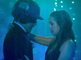 Image description: A man and a woman are close and dance. They are both wet from rain or water. The man is in a tux with a baseball helmet and a superhero mask. The women has dripping mascara and makeup. The time of day is evening.