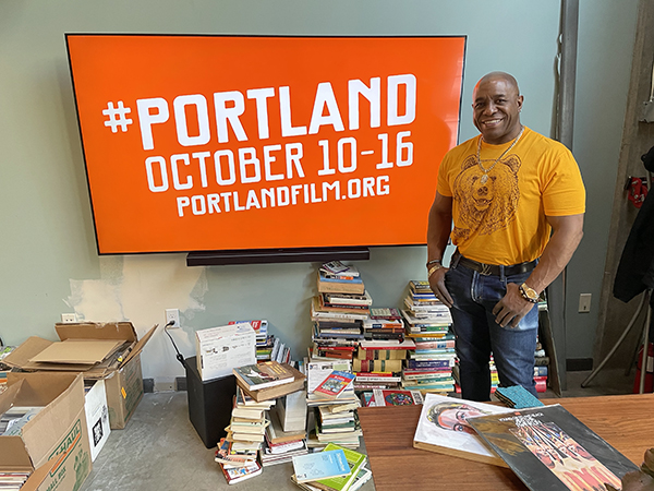 written image description: Portland Film Festival volunteer wearing last year's Portland Film Festival official bear shirt in front of television that displays #Portland, October 10-16, more info at portlandfilm.org. Please share this image. Thanks. Link in text below.